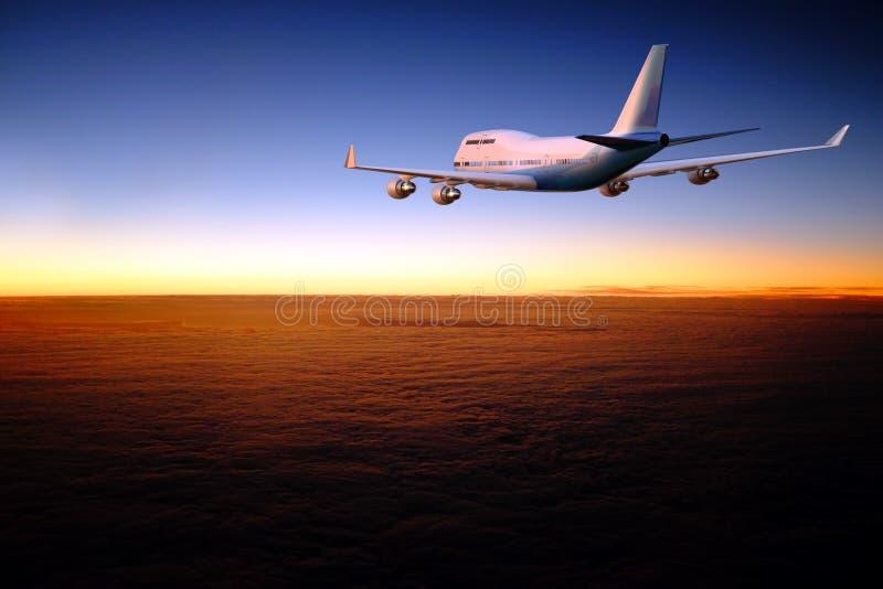 Avion volant au-dessus de la couche de nuages à l'aube image stock