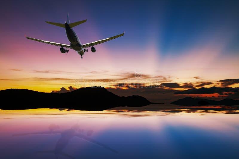 Avion volant au-dessus de la mer tropicale au beau coucher du soleil ou s léger photo libre de droits