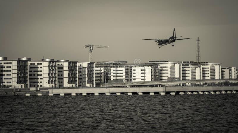 Avion volant au-dessus des bâtiments et de l'eau Préparez-vous au débarquement images stock
