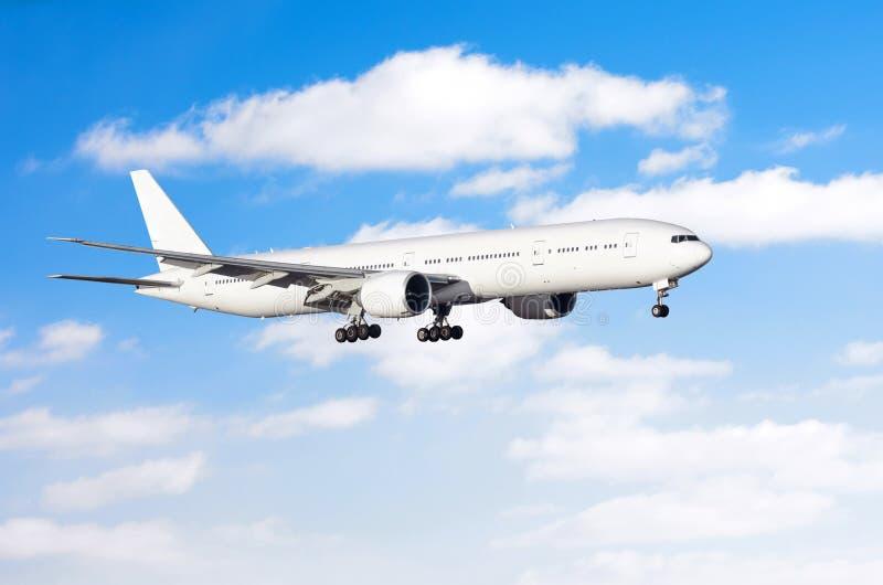 Aviones comerciales en acercamiento antes de aterrizar contra el cielo con las nubes fotos de archivo