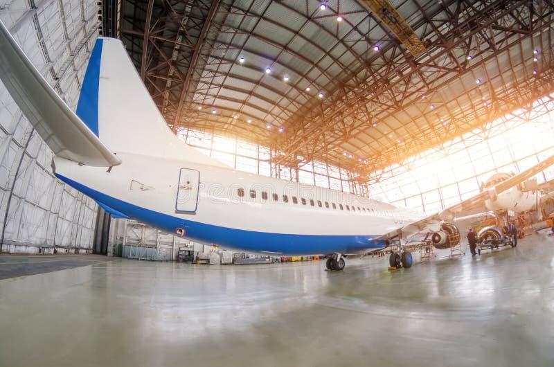 Aviones de pasajero en el mantenimiento de la reparación del motor y del fuselaje en hangar del aeropuerto Vista posterior, debaj imágenes de archivo libres de regalías
