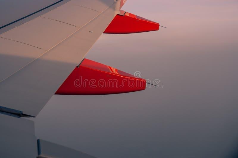 aviones del ala en la puesta del sol del cielo foto de archivo