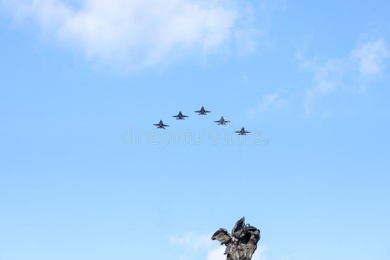 Aviones del avi?n de combate del RCAF de la fuerza a?rea canadiense real que vuelan en la formaci?n sobre la estatua del monument imágenes de archivo libres de regalías