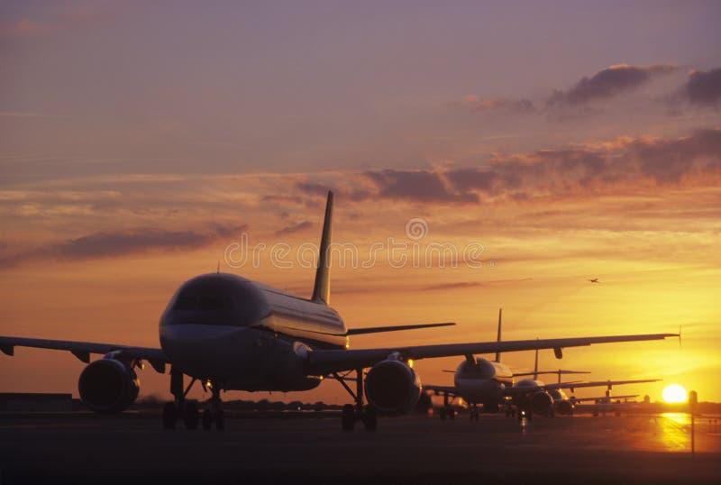 Aviones que se sientan en la pista de despeque en la puesta del sol imagen de archivo