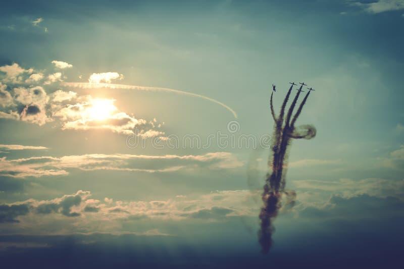 Avions acrobatiques faisant des acrobaties à un vol d'Airshow au coucher du soleil photos stock