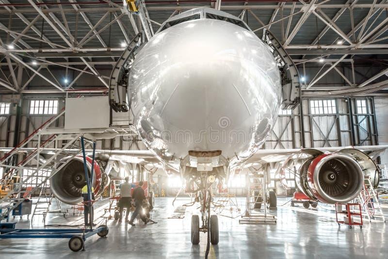 Avions de transport de passagers, fin de nez  Entretien de la réparation de moteur et de fuselage dans le hangar d'aéroport photos stock