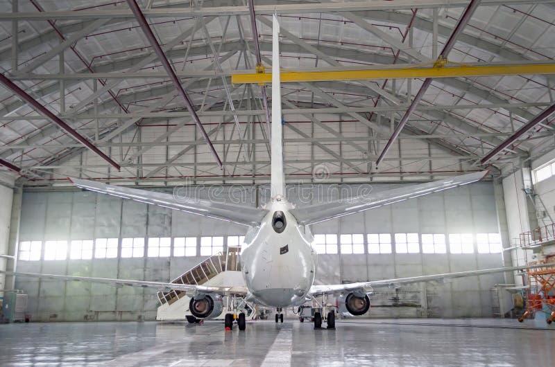 Avions de transport de passagers sur l'entretien de la réparation de moteur et de fuselage dans le hangar d'aéroport Vue arrière  images libres de droits