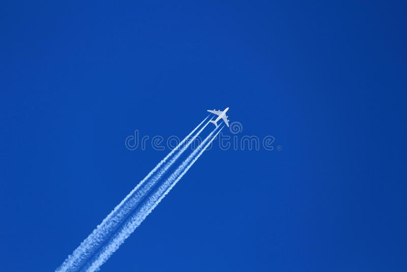 Avions en ciel profond-bleu avec la traînée photographie stock libre de droits