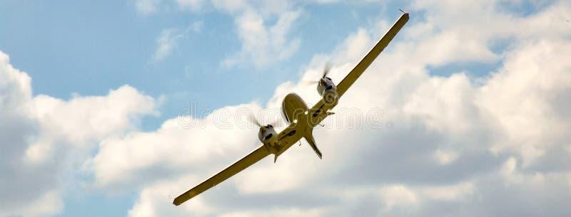 Avions jumeaux de piston de moteur pendant le tour avec la haute banque sur le ciel nuageux et ensoleillé image stock
