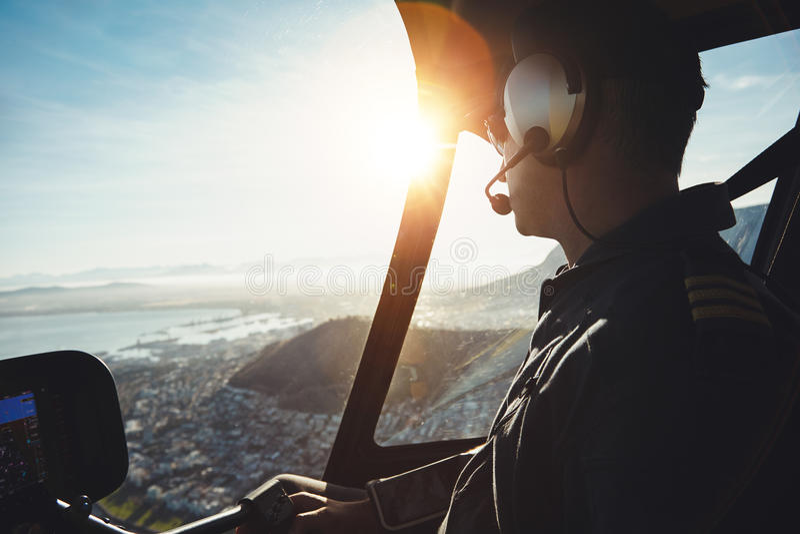 Avions pilotes de vol d'hélicoptère au-dessus d'une ville images stock