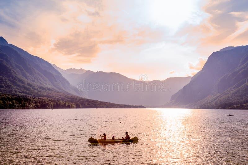 Aviron de famille dans le bateau de canoë sur le beau lac Bohinj, Slovénie image stock