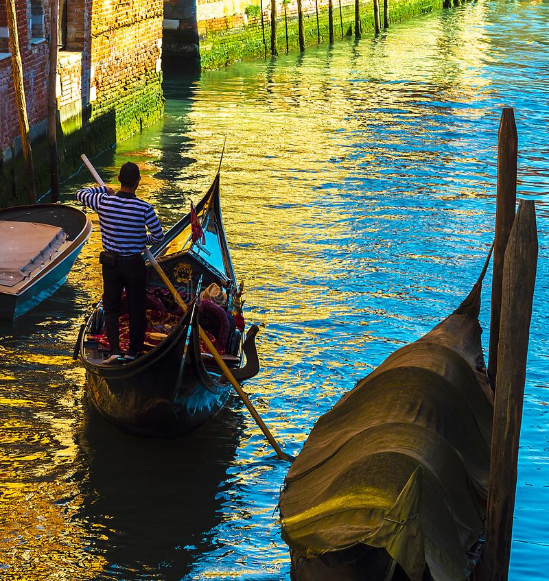 Aviron de gondolier sur sa gondole dans un canal vénitien un jour d'été photos stock