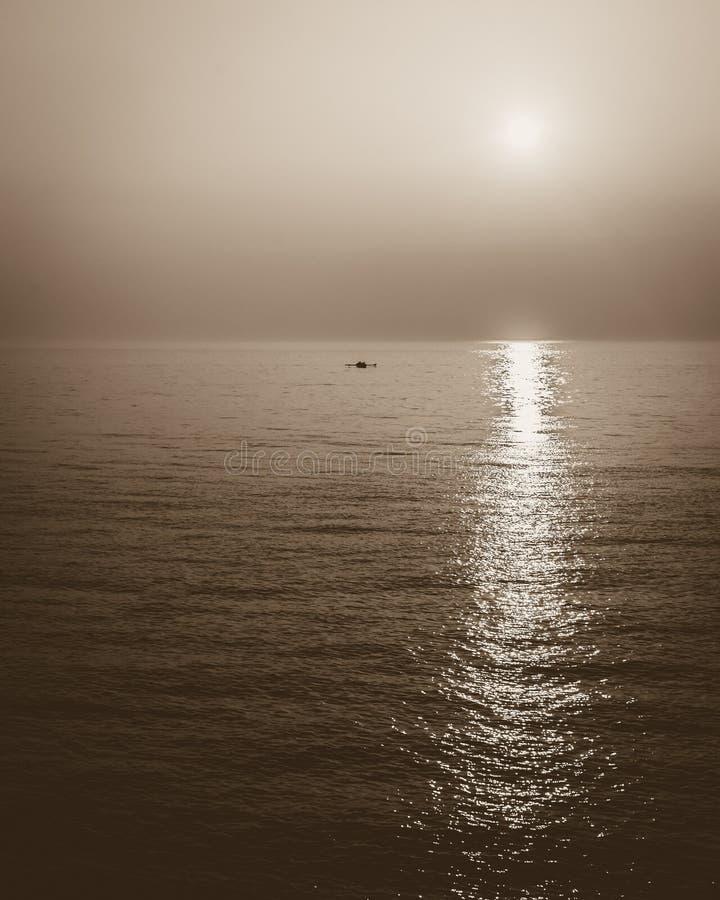 Aviron de l'équipage et du coucher du soleil dans la sépia image libre de droits