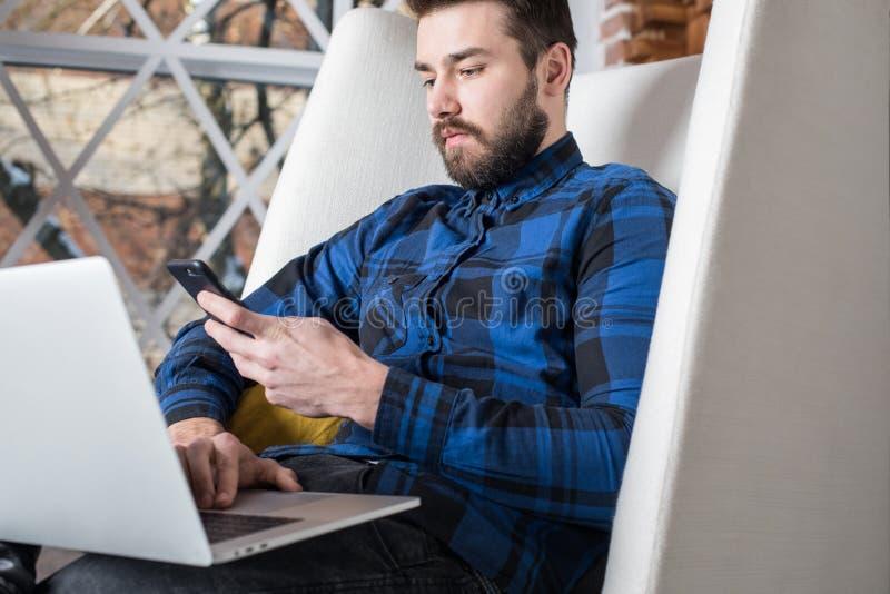 Avis de lecture d'homme d'affaires au téléphone portable pendant le webinar sur l'ordinateur portable image stock