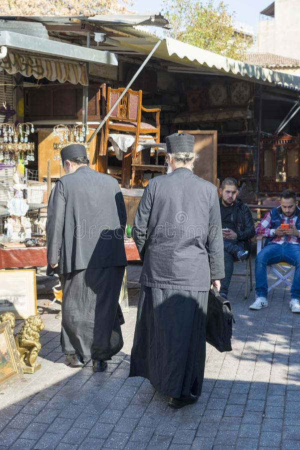 Avissinias Square. ATHENS, GREECE - OCTOBER 27, 2015: Flea market at Avissinias Square. Two Orthodox priests to bargain hunting stock photos