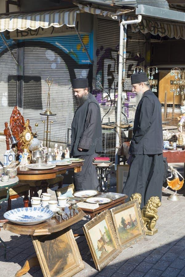 Avissinias Square. ATHENS, GREECE - OCTOBER 27, 2015: Flea market at Avissinias Square. Two Orthodox priests to bargain hunting stock photo