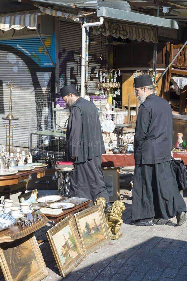 Avissinias Square. ATHENS, GREECE - OCTOBER 27, 2015: Flea market at Avissinias Square. Two Orthodox priests to bargain hunting royalty free stock image