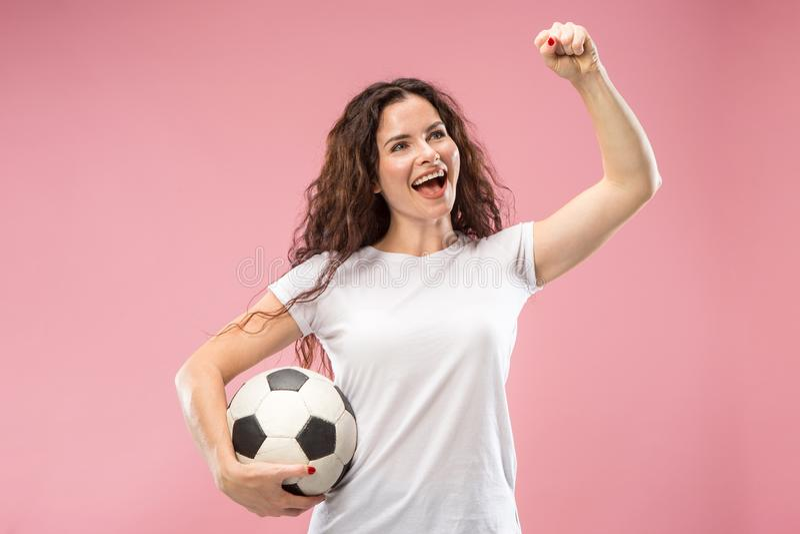 Avive al jugador de la mujer del deporte que celebra el balón de fútbol aislado en fondo rosado foto de archivo libre de regalías