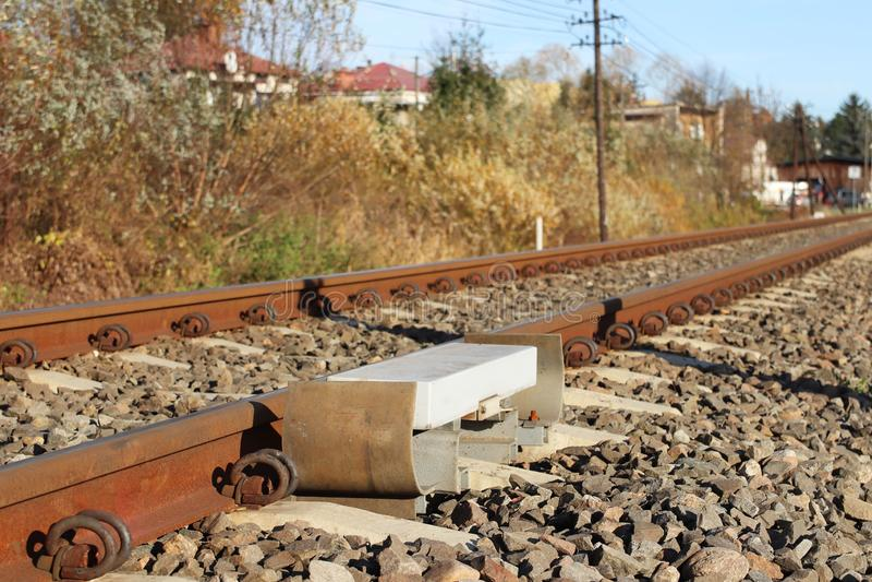 Avkännare som signalerar passagen av drevet på järnvägsspåret för att aktivera larmet på en vägkorsning Kulle av grovt grus royaltyfria bilder