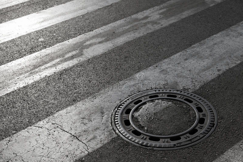 Avkloppmanhålräkning på asfaltvägen arkivbilder
