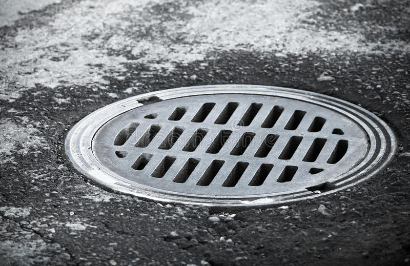 Avkloppmanhole på den stads- asfaltvägen royaltyfri bild