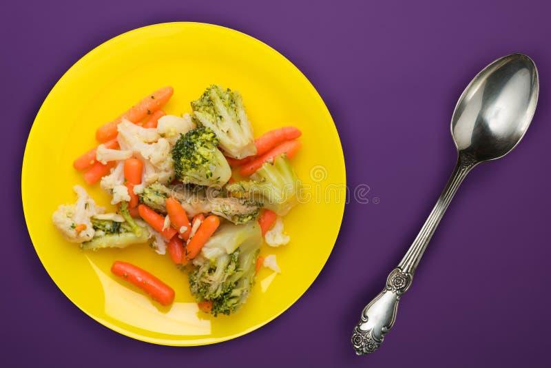 Avkomma grönsaker på en tallrik friterade grönsaker på en gul platta på en lila bakgrund broccoli och morötter på toppen av en pl arkivfoton