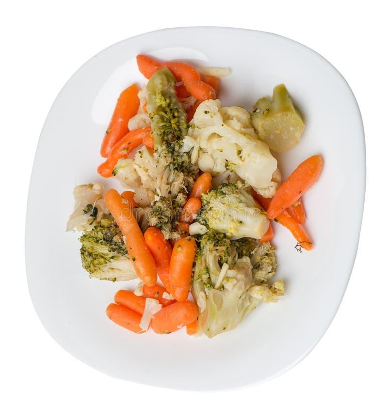 Avkomma grönsaker på en tallrik. Grålade grönsaker på en platta som är isolerad på vit bakgrund. broccoli och morötter på royaltyfria foton