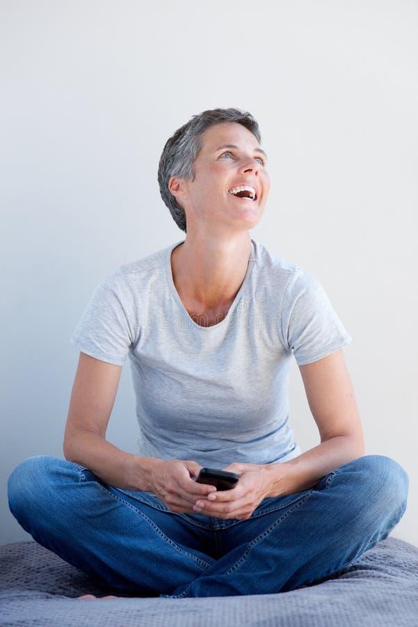 Avkopplad äldre kvinna som skrattar med mobiltelefonen royaltyfria bilder