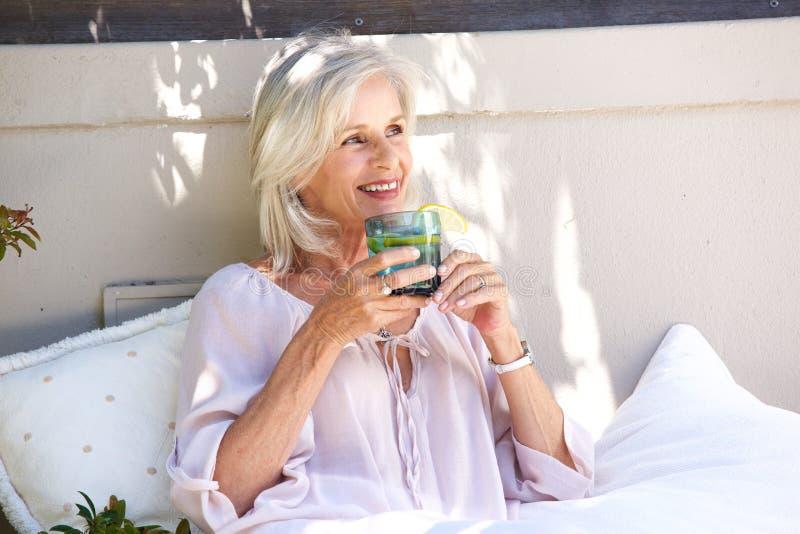 Avkopplad äldre kvinna utanför att dricka te med citronen fotografering för bildbyråer