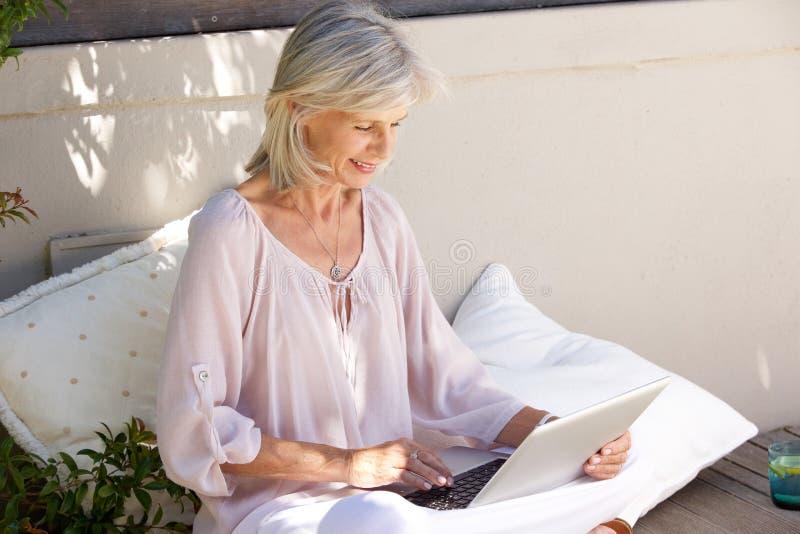 Avkopplad äldre kvinna utanför med bärbara datorn arkivbilder