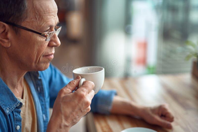 Avkopplad åldrig man som sitter i kafé med kaffe fotografering för bildbyråer