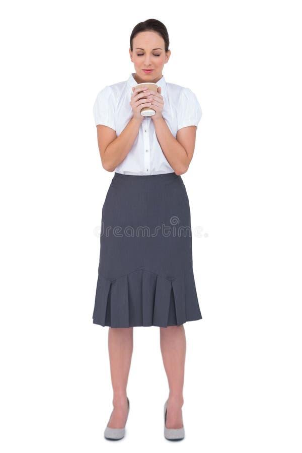 Avkopplad affärskvinna som luktar kaffe royaltyfri bild