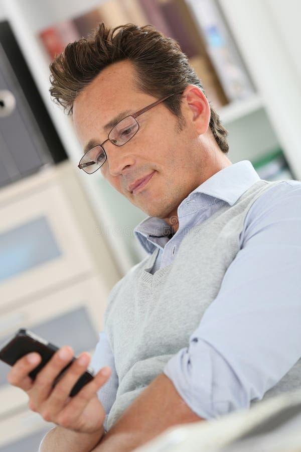Avkopplad affärsman på kontoret genom att använda smartphonen royaltyfria bilder