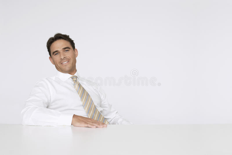 Avkopplad affärsman Sitting At Desk i regeringsställning royaltyfri bild