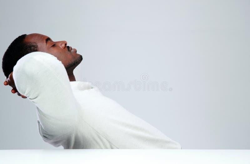 Avkopplad afrikansk man som sleaping på hans arbetsplats royaltyfria foton