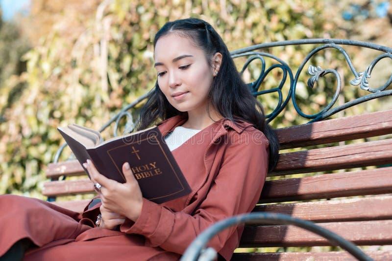 Avkopplad asiatisk flicka som läser den heliga bibeln på luft royaltyfri fotografi