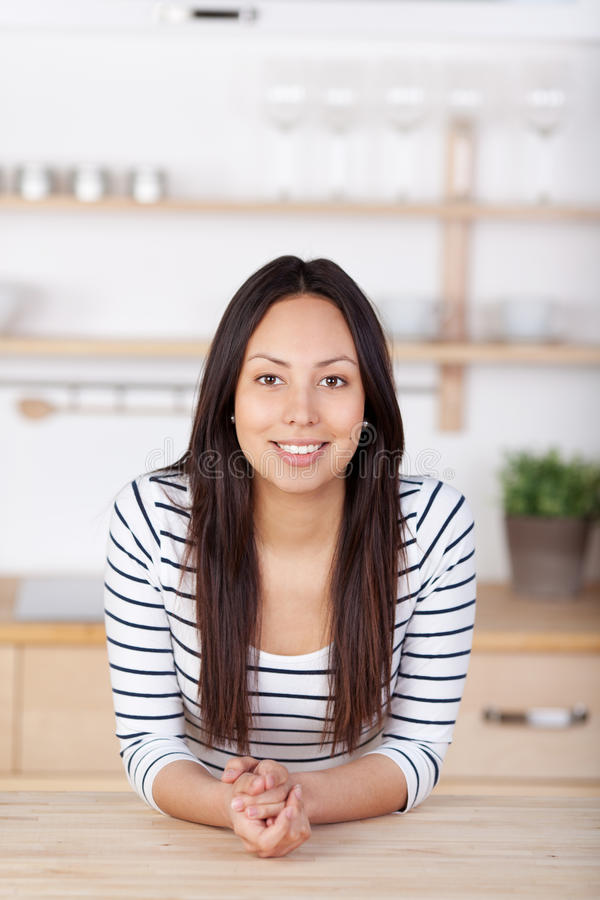 Avkopplad benägenhet för ung kvinna på köksbordet arkivfoto