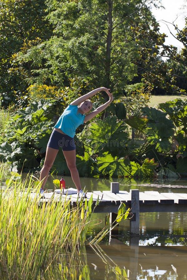 Avkopplad blond flicka som sträcker på en träbro och ett vatten royaltyfri foto