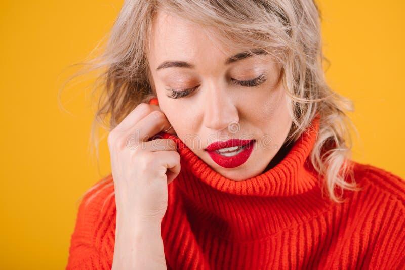 Avkopplad fundersam romantisk blobdekvinnastående i rött förkläde Gul bakgrund arkivfoton