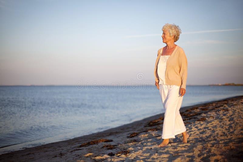 Avkopplad gammal dam som strosar på stranden arkivbild