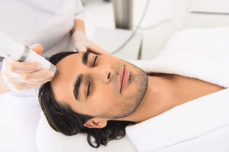 Avkopplad grabb som får elektrisk ansikts- massage royaltyfri bild
