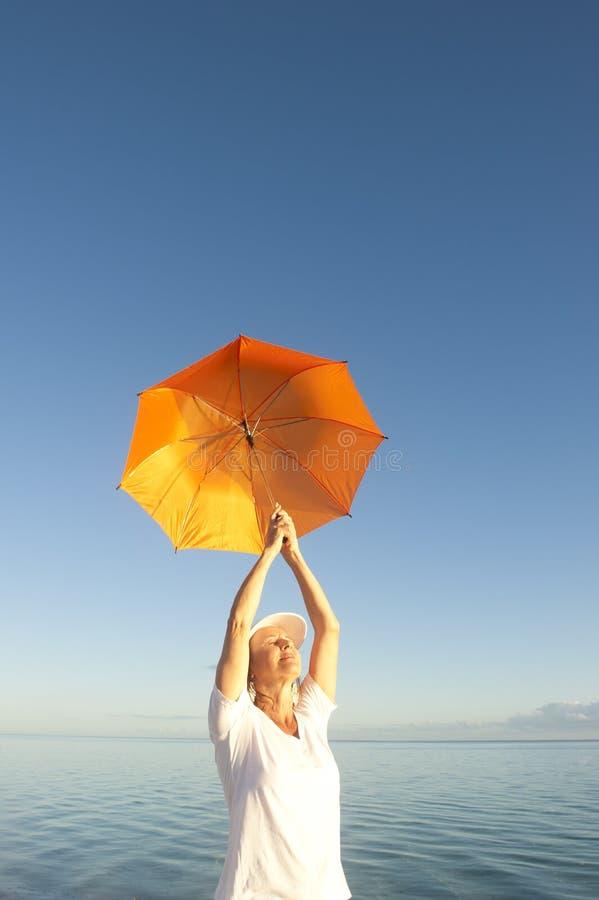 Avkopplad hög kvinna på havbakgrund royaltyfri fotografi