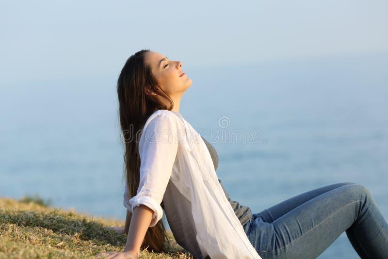 Avkopplad kvinna som andas sammanträde för ny luft på gräset royaltyfria bilder