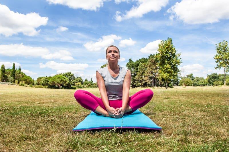 Avkopplad kvinna som gör yoga med övrekroppen på övning royaltyfri foto