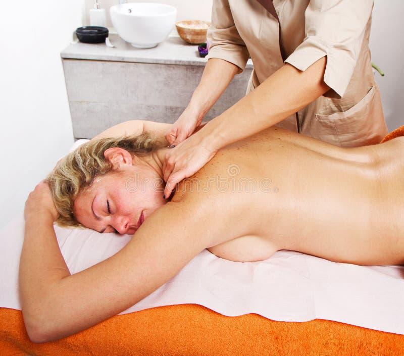 Avkopplad kvinna som har en massage i en skönhetmitt arkivfoto