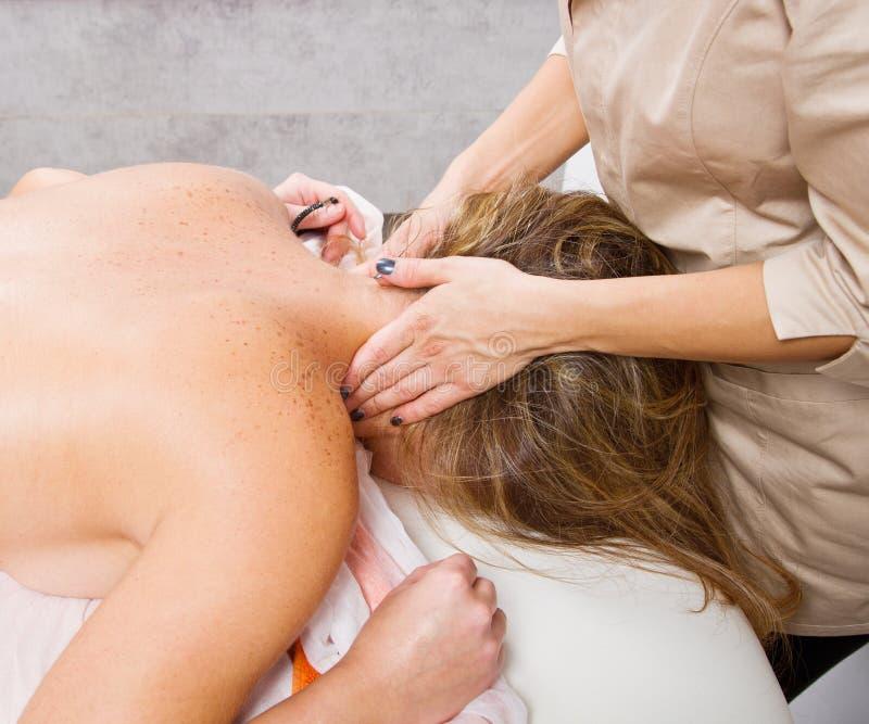 Avkopplad kvinna som har en massage i en skönhetmitt arkivbilder