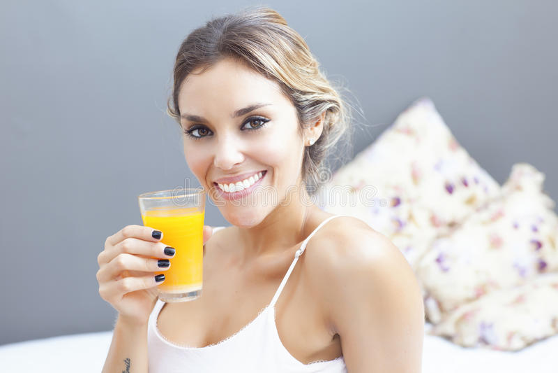 Avkopplad kvinna som hemma dricker orange fruktsaft i sovrum royaltyfri bild