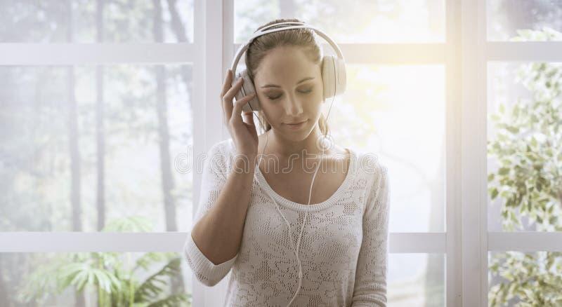 Avkopplad kvinna som hemma lyssnar till musik royaltyfri bild
