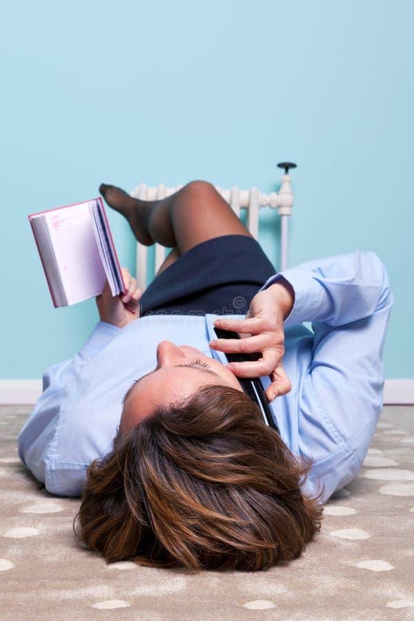 Avkopplad kvinna som ligger prata ner på telefonen arkivbild