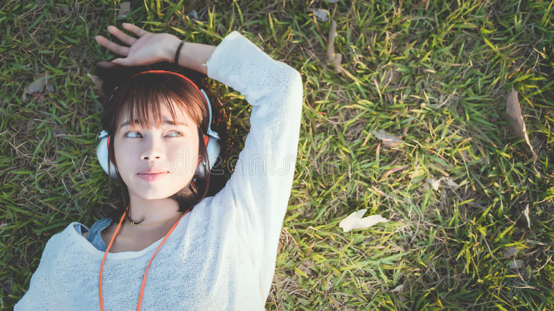 Avkopplad kvinna som lyssnar till musiken med att ligga för hörlurar fotografering för bildbyråer